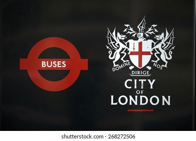 LONDON, UK - APRIL 06: Detail of black City of London banner in bus stop featuring its coat of arms next to the Transport for London red logo. April 06, 2015 in London.