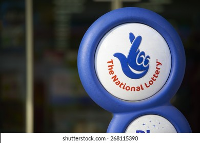 LONDON, UK - APRIL 07: Close up of blue National lottery sign in front of shop, showing its crossed fingers logo. On 07 April 2015.