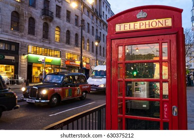 LONDON, UK - APRIL 10, 2007: Red telephone box and black cab in one of the central streets of the city in evening.