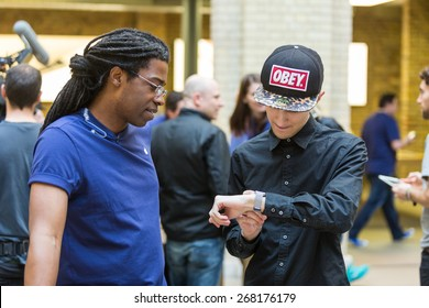 LONDON, UK - APRIL 10, 2015: Customers looking at and wearing brand new Apple Watches at Covent Garden Apple store.
