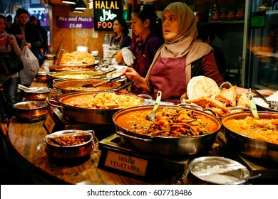 LONDON, UK - APRIL 10, 2016: Traders at a market stall selling curry and varieties of cooked foods at Camden Market.