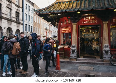 London, UK - April 13, 2019: People walking past restaurants in Chinatown, London. Chinatown is home to a large East Asian community and is famous for its eateries and events.