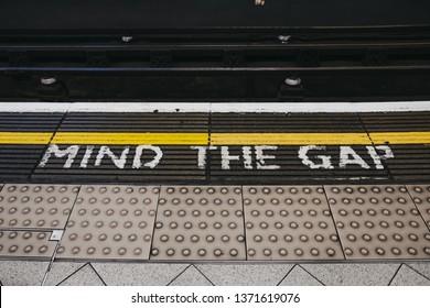 London, UK - April 13, 2019: Mind the gap sign an a platform of Embankment underground station. London Underground is the oldest underground railway in the world.