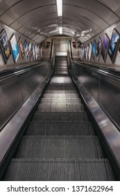 London, UK - April 13, 2019: View down the escalator leading to the platform of Embankment underground station. London Underground is the oldest underground railway in the world.