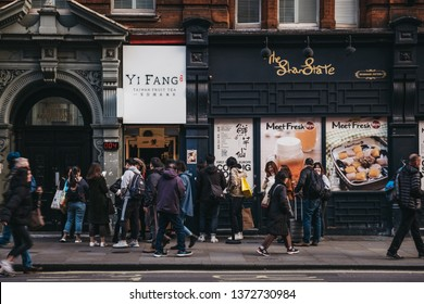 London, UK - April 13, 2019: People queuing to buy Taiwan fruit tea from Yi Fang shop in Chinatown, London. Chinatown is home to an East Asian community and is famous for its eateries and events.