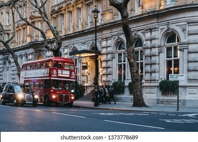 London, UK - April 13, 2019: Black cab and an afternoon tea bus tour inside retro red double decker bus on a street in London, UK, at dusk. Double decker bus is an iconic symbol of the city.