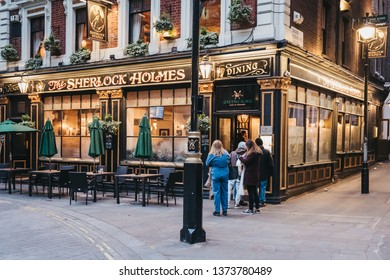 London, UK - April 13, 2019: People entering Sherlock Holmes pub in London, a traditional English pub with Holmes-themed memorabilia, restaurant and roof garden.