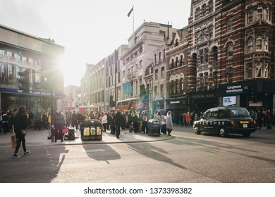 London, UK - April 13, 2019:People walking near Tottenham Court Road station at sunset and rain. Tottenham Court Road is a London Underground and a future Elizabeth line station in West End of London.