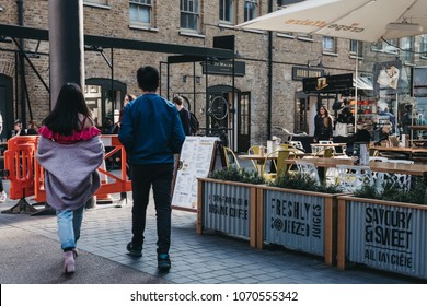 LONDON, UK - APRIL 14, 2018: People walking past market stalls in Old Spitalfields Market, one of the finest surviving Victorian Market Halls in London with stalls offering fashion, antiques and food.