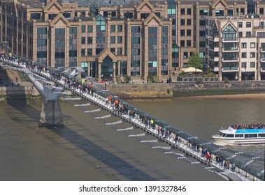 LONDON, UK - APRIL 14, 2019: People walking on the  Millenium bridge over river Thames with boat approaching