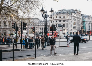 London, UK - April 14, 2019: People waiting to cross the road next to Trafalgar Square, a public square in Charing Cross area of London that features some of London's top attractions.