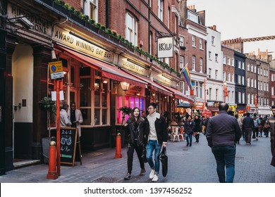 London, UK - April 14, 2019: People walking past Ku Bar, one of the largest gay bars in London located just off Leicester Square.