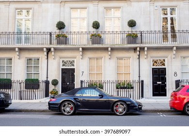 LONDON, UK - April, 14: Luxury black Porsche. Houses in London, english architecture