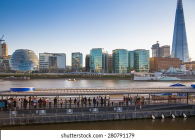 LONDON, UK - APRIL 15, 2015: Modern buildings on the south bank of river Thames walk in sunset. Office centre, theatre and London city hall building