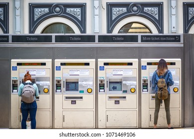 London, UK - April 17, 2018 - Passengers purchasing train tickets from machines at London Paddington station