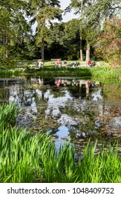 London, UK - April 18, 2014. Visitors enjoy the view of the Waterlily Pond at Kew Botanic Gardens. The gardens were founded in 1840