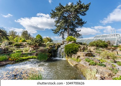 London, UK - April 18, 2014. Rock garden and Princess of Wales Conservatory in Kew Botanic Gardens. The gardens were founded in 1840 and are of international significance for botanical research.