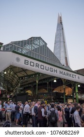 LONDON, UK - APRIL 19, 2018: crowds of people having after-work drinks at one of the entrances to Borough Market, with The Shard visible in the background.