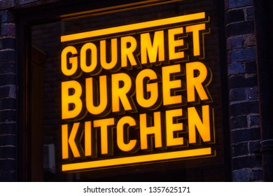 London, UK - April 1st 2019: The company logo of Gourmet Burger Kitchen above the entrance to one of their restaurants in London, UK.