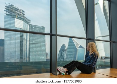London, UK - April 20, 2019: A young adult looks out at a view of London's modern city skyline.