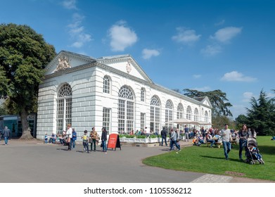London, UK - April 2018: The classic white building of The Orangery restaurant and cafe setting among lush botanic area at Kew Gardens in Richmond upon Thames, England