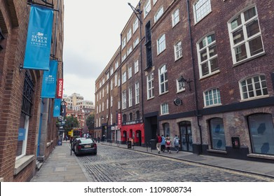 London, UK - April 2018: Cobbled alley of Earlham Street seen from the Seven Dials located between Soho and Covent Garden along with historic buildings that house retail stores and restaurant