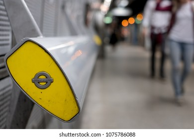 London UK. April 2018. In foreground, end of handrail at Westminster underground station, London showing TFL roundel. In background blurred commuters walking along platform, with train behind.