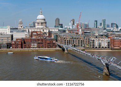 London, UK - April 2018: London Millennium Bridge, suspension footbridge crossing the River Thames linking Bankside with the City of London, with skyline of London and St Paul Cathedral in background