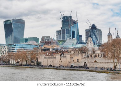 London, UK - April 2018: Tower of London located by the River Thames with skyscrapers and buildings constructed in modern architectural style rising up the behind skyline
