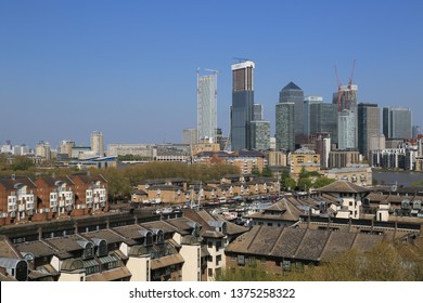 London / UK - April 20th 2019: Greenland Quay / Dock in Canada Water Surrey Quays London next to the river thames, London's skyline including Canary Wharf in the background on a clear sunny day