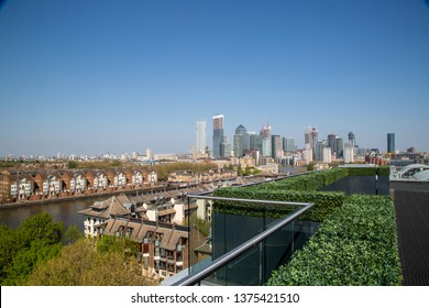 London / UK - April 20th 2019: Greenland Quay / Dock in Canada Water Surrey Quays London next to the river thames, London's skyline, Canary Wharf in the background. Photo taken from roof garden.