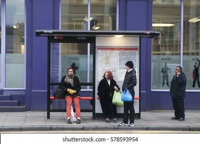 LONDON, UK - APRIL 22, 2016: People of different nationalities are waiting for the bus at the stop in front of a blue wall construction