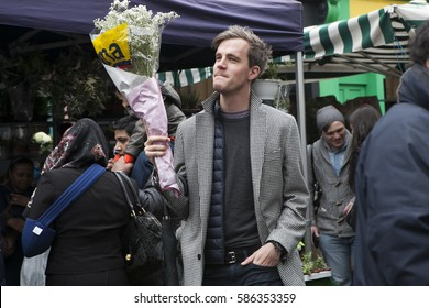 LONDON, UK - APRIL 22, 2016: A smiling young man in a coat with a bouquet of white flowers at Columbia flower market