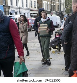 LONDON, UK - APRIL 22, 2016: serious man carries a stack of books on Brick Lane