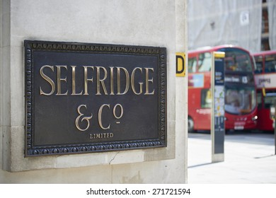 LONDON, UK - APRIL 22: Shop sign at the corner of famous department store Selfridge & Co., in Oxford Street, with red double-decker bus in the background. April 22, 2015 in London.