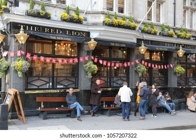 LONDON, UK - APRIL 23, 2012: People visit The Red Lion pub in London. It is a typical London pub. There are more than 7,000 pubs in London.