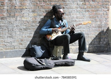 London, UK - April 25th 2015: Man busking with electric guitar on street in Shoreditch, London