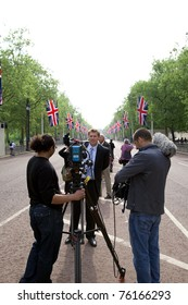 LONDON, UK - APRIL 26: An unidentified news team films prior to the Royal Wedding on April 26, 2011. They are along The Mall towards Buckingham Palace in London, UK. The Royal Wedding will be widely covered in the media.