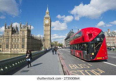 LONDON, UK - APRIL 27, 2015: Modern double-decker bus passes pedestrians walking in front of Big Ben and Houses of Parliament on Westminster Bridge.