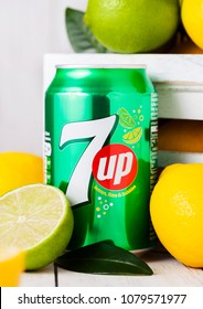 LONDON, UK - APRIL 27, 2018: Aluminium can of 7UP lemonade soda drink with fresh lemons and limes.This refreshment drink produce Pepsi company.