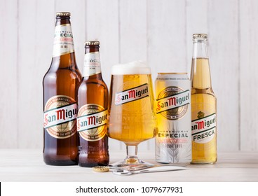 LONDON, UK - APRIL 27, 2018: Glass bottles of San Miguel lager beer on wooden background with original glass. The San Miguel brand of beer is the leading brand of the San Miguel Brewery Inc.