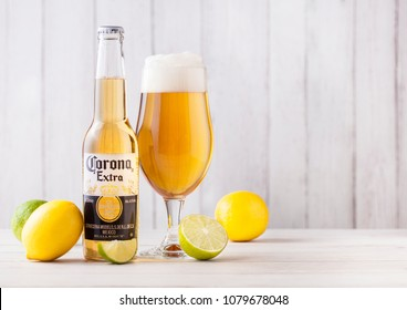 LONDON, UK - APRIL 27, 2018: Bottle of Corona Extra Beer on wooden background with fresh lemons and limes . Corona, produced by Grupo Modelo.