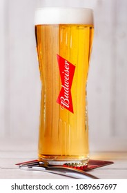 LONDON, UK - APRIL 27, 2018: Original glass of Budweiser Beer on wooden background with bottle opener. An American lager first introduced in 1876.