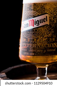 LONDON, UK - APRIL 27, 2018: Original glass of San Miguel lager beer on dark wooden background. The San Miguel brand of beer is the leading brand of the San Miguel Brewery Inc.