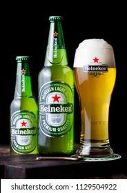 LONDON, UK - APRIL 27, 2018: Bottles and original glass of Heineken Lager Beer on dark wooden background. Heineken is the flagship product of Heineken International
