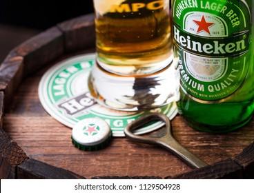 LONDON, UK - APRIL 27, 2018: Original glass and bottle of Heineken Lager Beer on top of old wooden barrel with coaster and bottle opener. Heineken is the flagship product of Heineken International