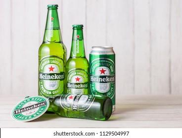 LONDON, UK - APRIL 27, 2018: Bottles and aluminium cans of Heineken Lager Beer on wooden background. Heineken is the flagship product of Heineken International