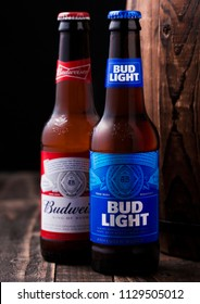 LONDON, UK - APRIL 27, 2018: Glass bottle of Bud Light and Budweiser original beer next to old wooden barrel., an American lager first introduced in 1876.