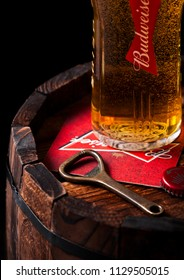 LONDON, UK - APRIL 27, 2018: Original glass of budweiser beer with beer coater and bottle opener on wooden barrel., an American lager first introduced in 1876.
