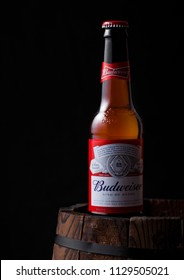 LONDON, UK - APRIL 27, 2018: Glass bottle of Budweiser original beer on top of old wooden barrel, an American lager first introduced in 1876.
